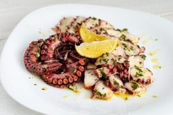 Delicious octopus carpaccio with dressing on white plate. Seafood delicacy
