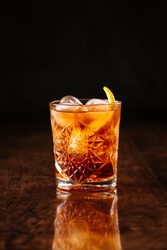 delicious old fashion cocktail in the etched glass with ice and orange slices, dark wooden background, vertical, side view
