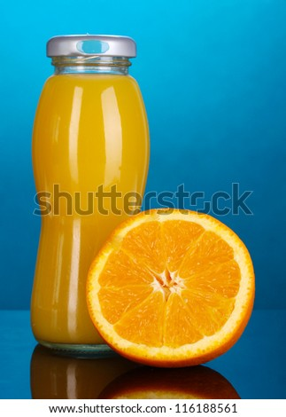 Delicious orange juice in a bottle and orange next to it on colorful background