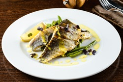 Delicious oven baked fish or grilled fillet or steak with lemon for a nutritious seafood dinner. walleye fillet and asparagus