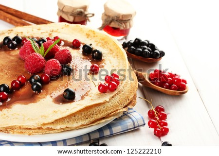 Delicious pancakes with berries and jam on plate on wooden table
