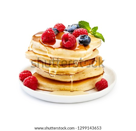 Photo of  Delicious pancakes with berries, honey or maple syrup. Homemade pancakes and sweet syrup on white plate isolated.