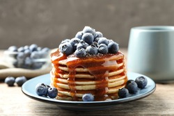 Delicious pancakes with fresh blueberries and syrup on wooden table