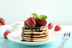 Delicious pancakes with fresh strawberries and chocolate syrup on light blue wooden table