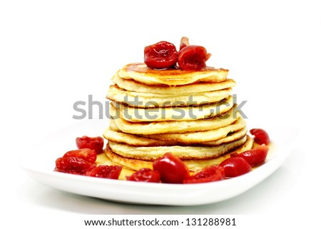Delicious pancakes with maple syrup and sweet cherries