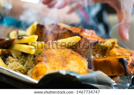 Delicious paneer, french fries and vegetble sizzler giving off smoke and steam. This dish is a favorite in north india and comes in vegetarian and non vegetarian variants and various ingridients