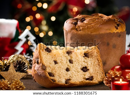 Delicious Panettone slice with candied fruits with blinking blurred christmas lights. Chocottone