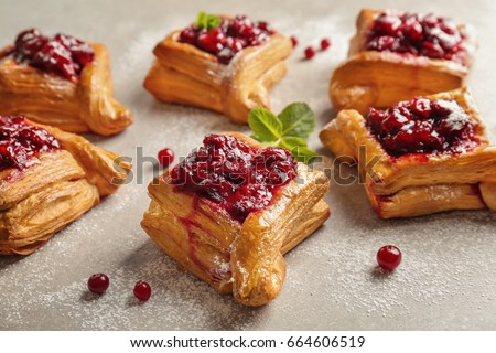 Delicious pastries with cherry jam on light background #664606519