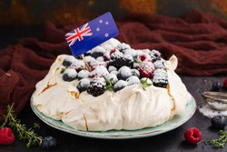 Delicious Pavlova cake with cream, berries thyme and New Zealand flag over dark background. Space for text. Selective focus