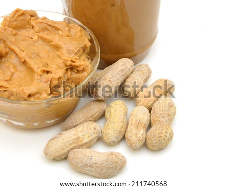 Delicious peanut butter in jar of peanut near isolated and glass bowl on white