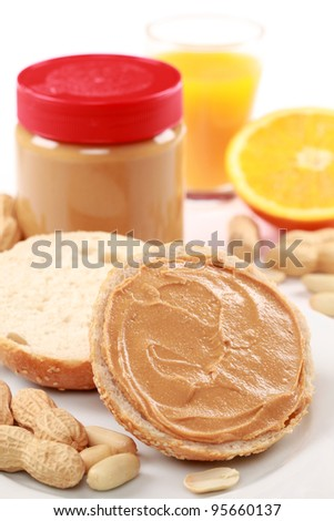 Delicious peanut butter on a bun and a jar in the background