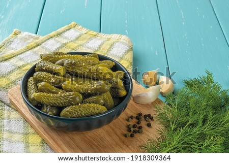 Delicious pickled cornichons in a dark ceramic bowl, garlic, pepper and dill over blue wooden table. Whole green gherkins marinated with dill and mustard seeds. Delicious baby pickles.  Photo stock ©