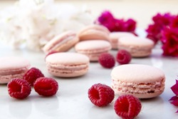 Delicious pink biscuits macaroons on light background with fresh berries raspberry. A romantic date. Gift for Valentine's day. Ideal for holiday of international women's day.