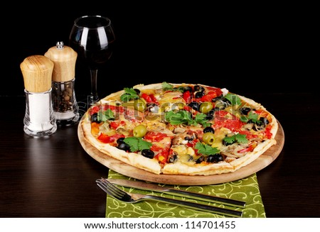 Delicious pizza with glass of red wine and spices on wooden table on black background