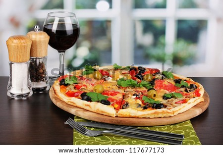 Delicious pizza with glass of red wine and spices on wooden table on window background