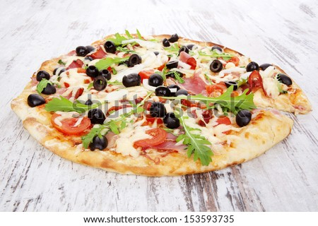 Delicious pizza with ham, black olives, fresh herbs and melted cheese on white wooden background. Traditional rustic style pizza eating.