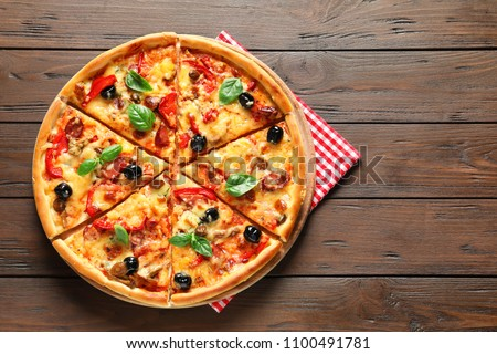 Delicious pizza with olives and sausages on wooden table, top view
