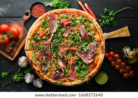 Delicious pizza with prosciutto and arugula. Italian snacks. Top view. Free space for your text. Foto stock ©
