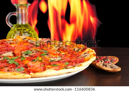 delicious pizza with vegetables and salami on wooden table on flame background - stock photo