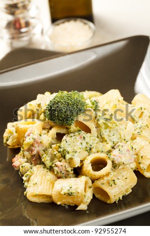 Delicious plate of macaroni pasta with broccoli and sausage in  a modern dishware and table setting