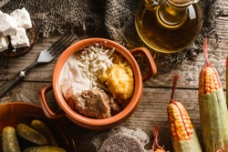 Delicious polenta with meat, cheese and sour cream in bowl on rustic wooden background. Traditional Romanian food, top view