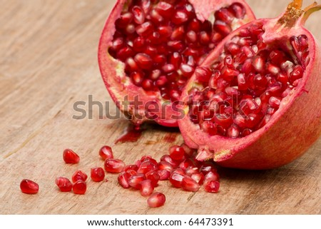 Delicious pomegranate with seeds on wooden table