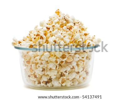 Delicious popcorn in glass bowl over white background