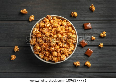 Delicious popcorn with caramel in bowl and candies on wooden background, top view #1096377791