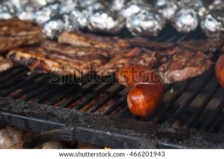 Delicious pork meat and sausages on the barbecue grill. #466201943