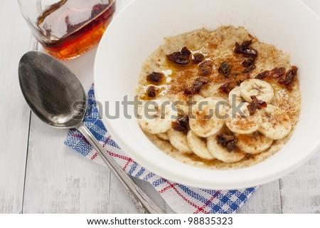 delicious porridge with banana, dates, cinnamon and maple syrup - stock photo