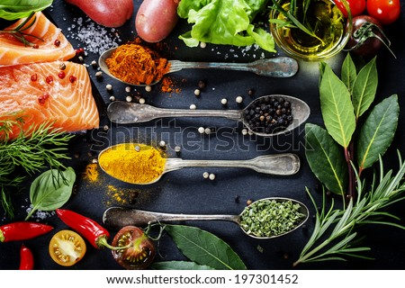 Delicious portion of fresh salmon fillet with aromatic herbs spices and vegetables healthy food diet or cooking concept