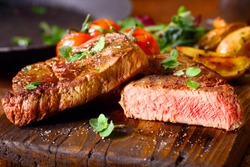 Delicious portion of healthy grilled lean medium rare beef steak cut through and served on a wooden kitchen board garnished with fresh herbs