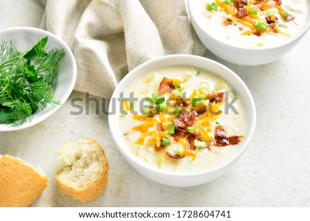 Delicious potato creamy soup with bacon and cheddar cheese in bowl on light stone background. Healthy diet dish for dinner. Close up view