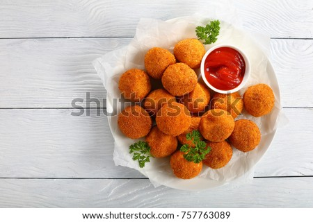 delicious potato croquettes - mashed potatoes balls with grated mozzarella cheese seasoned with spices; breaded and deep fried in olive oil, served with ketchup on white plate, view from above
