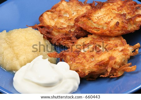 Delicious potato latkes for Hanukah, served on a plate with sour cream and applesauce.