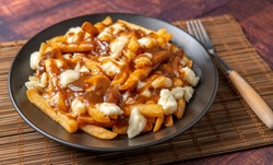 Delicious Poutine with cheese curds french fries on the table. so juicy and yummy