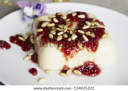 Delicious pudding with seeds and strawberry jam. On a table. Natural lighting