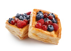 Delicious puff pastries with berries on white background