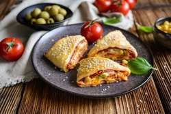 Delicious puff pastry pizza triangle rolls stuffed with tomato sauce, ham, cheese, corn, olives and sprinkled with sesame seeds
