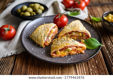 Delicious puff pastry pizza triangle rolls stuffed with tomato sauce, ham, cheese, corn, olives and sprinkled with sesame seeds ストックフォト ©