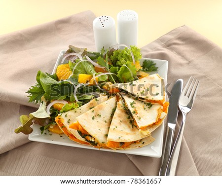 Delicious pumpkin quesadilla sliced and ready to serve with a garden salad.