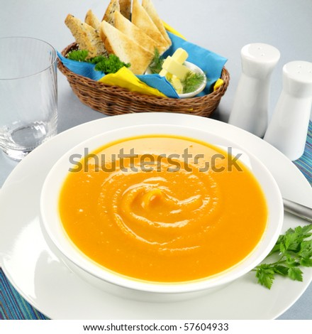 Delicious pumpkin soup with a selection of toasts with butter.