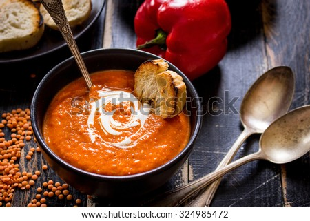 Delicious pumpkin soup with heavy cream on dark rustic wooden table with red bell pepper, bread toasts, lentil, tomatoes