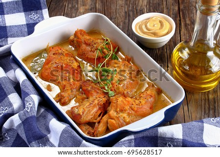 delicious Rabbit braised in mustard sauce in gratin dish with bottle of olive oil on wooden table, authentic recipe, close-up