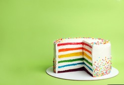Delicious rainbow cake on color background