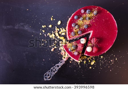 Delicious raspberry cake with fresh strawberries, raspberries, blueberry, currants and pistachios on wooden background. Free space for your text.