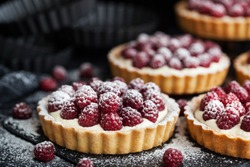 Delicious raspberry mini tarts (tartlets) with whipped cream on dark background