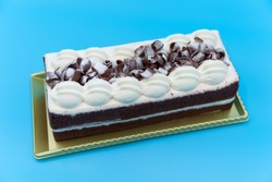 Delicious rectangular chocolate cake with icing and grated chocolate. Isolated on blue background. Top view. Horizontal shot.