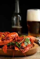 Delicious red boiled crayfishes and beer on wooden table, closeup