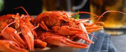 Delicious red boiled crayfishes on table, closeup. Banner design